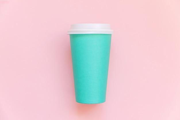 Просто плоский дизайн лежал голубой бумажной кофейной чашке на розовом пастельном красочном модном фоне