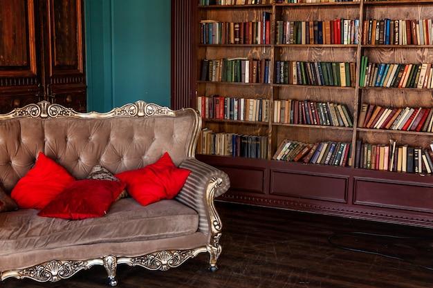 ホームライブラリの豪華なクラシックなインテリア。本棚、本、アームチェア、ソファ、暖炉のある応接間。