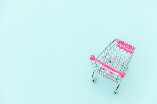 青のパステル調のカラフルなトレンディな背景に分離された車輪付きショッピンググッズの小さなスーパーマーケット食料品プッシュカート