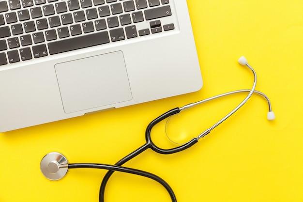 黄色に分離された聴診器キーボードラップトップコンピューター