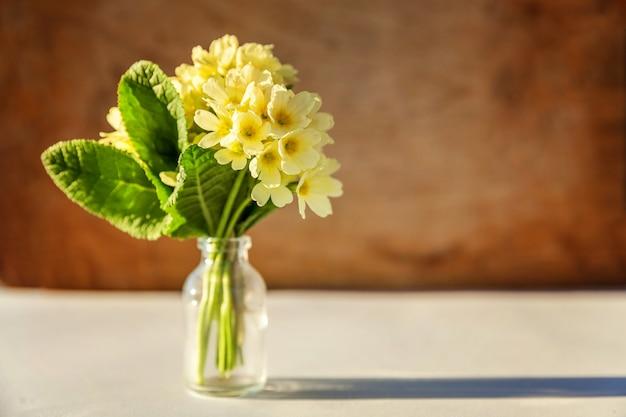 イースターのコンセプト。木製のガラスの花瓶に黄色の花とプリムローズプリムラの花束