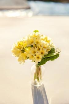 イースターのコンセプト。ガラスの花瓶に黄色の花とプリムローズプリムラの花束