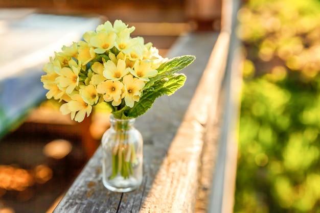 イースターのコンセプト。柔らかい日光の下でガラスの花瓶に黄色の花とプリムローズプリムラの花束