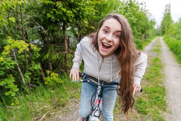 夏都市公園屋外で若い女性乗馬自転車。