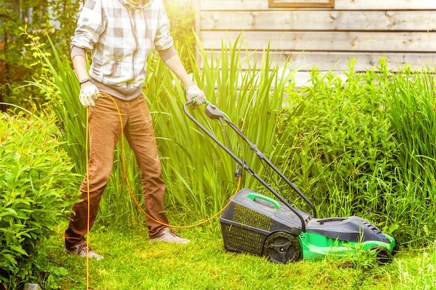 裏庭の芝刈り機で緑の草を切る男。