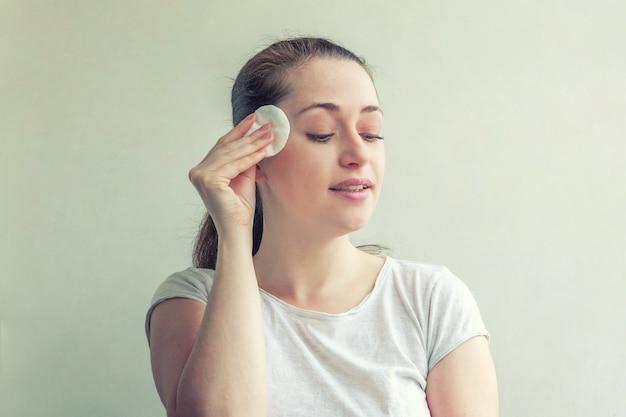 Улыбающаяся женщина с удалением мягкой здоровой кожи с ватным тампоном