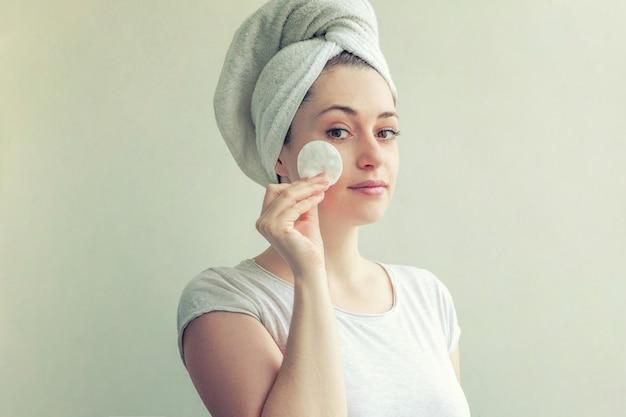 Улыбающаяся женщина в полотенце на голове с мягкой здоровой кожей удаляет макияж с ватным тампоном