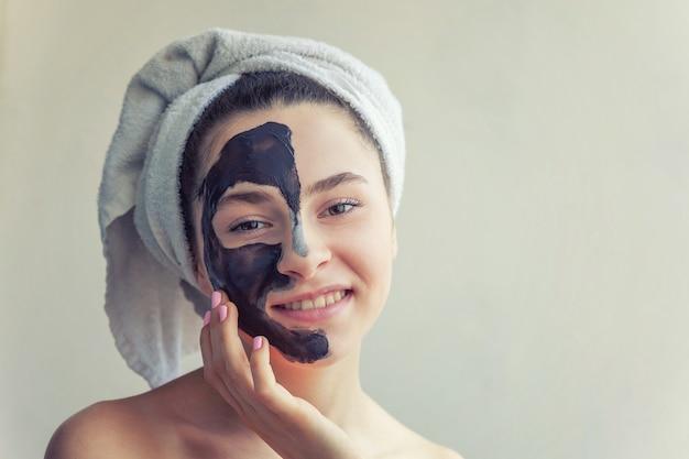 Женщина наносит черную питательную маску на лицо