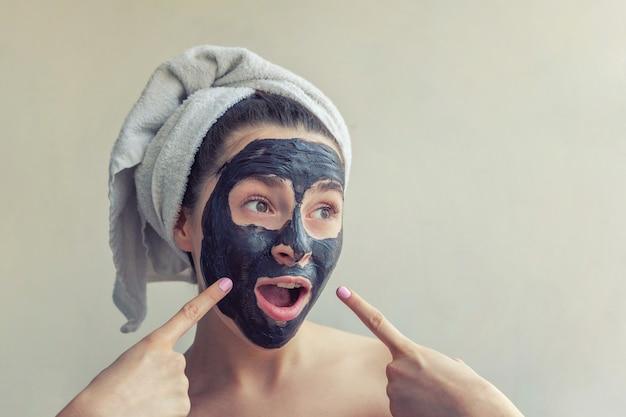 女性の顔に黒い栄養マスクを適用します。