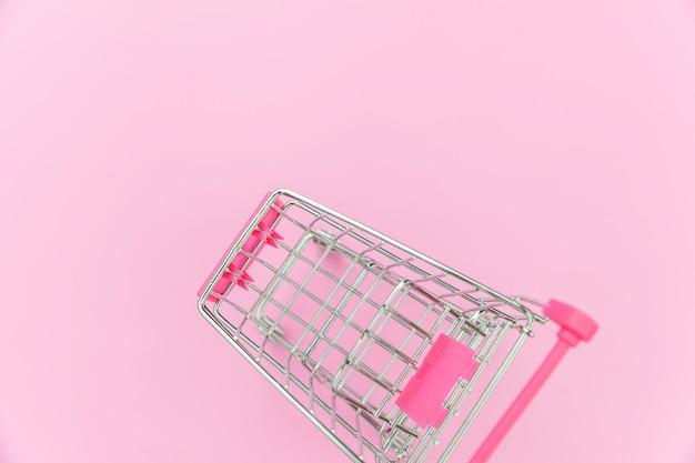 ピンクのパステル調のカラフルなトレンディな背景に分離された車輪付きショッピンググッズの小さなスーパーマーケット食料品プッシュカート。販売購入モールマーケットショップ消費者概念。コピースペース。