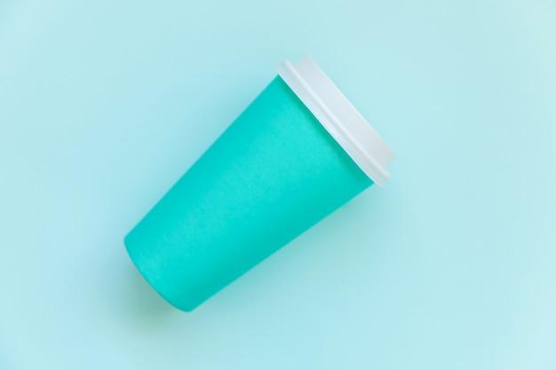 Просто плоский дизайн лежал голубой бумажной кофейной чашке на синем пастельном красочном модном фоне