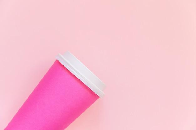 Просто плоский дизайн лежал розовой бумажной чашке кофе на розовом пастельном красочном модном фоне