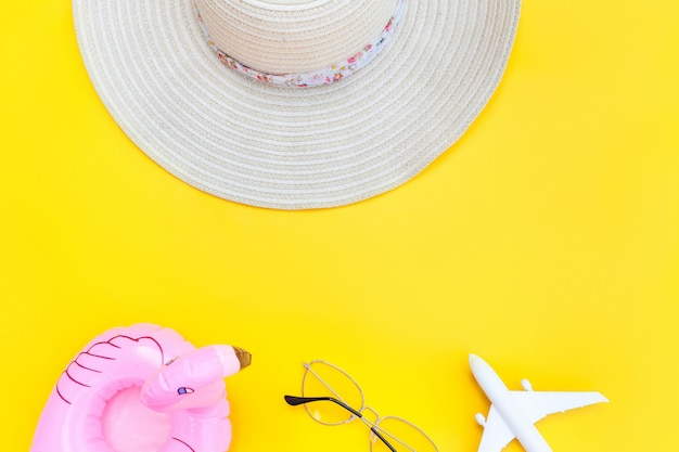 夏のビーチの組成。平面サングラス帽子と黄色の背景に分離されたインフレータブルフラミンゴと最小限のシンプルなフラットレイアウト。休暇旅行の冒険旅行のコンセプト。トップビューコピースペース。