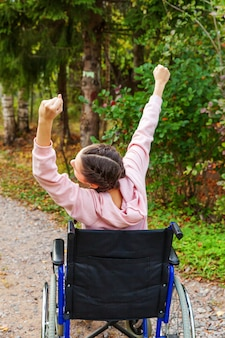 自由を楽しんでいる病院公園の道で車椅子の若い幸せなハンディキャップの女性。自然の中で屋外の障害者のための無効な椅子で麻痺した少女。リハビリテーションの概念。
