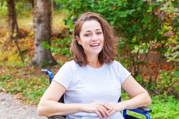 患者サービスを待っている病院の公園の道路で車椅子の若い幸せなハンディキャップの女性。自然の中で屋外の障害者のための無効な椅子で麻痺した少女。リハビリテーションの概念。