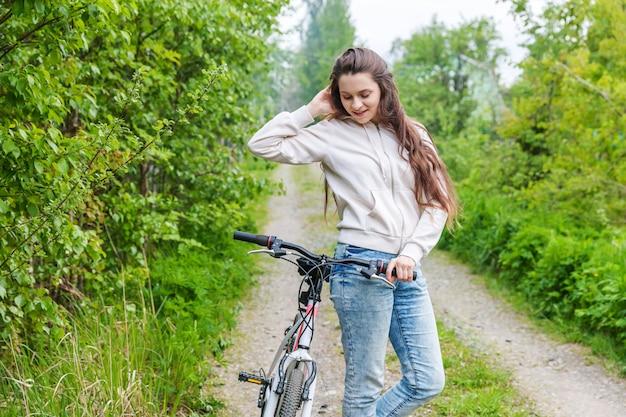 夏の都市公園屋外で若い女性乗馬自転車。アクティブな人々。内気な少女のリラックスとライダーバイク