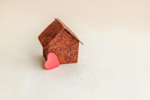 赤いハートのミニチュアグッズモデル家。エコビレッジの抽象的な環境背景。不動産抵当財産保険の甘い夢の家の生態学の概念