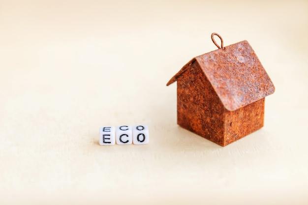 碑文エコ文字単語とミニチュアグッズモデルの家。エコビレッジ、抽象的な環境背景。エコロジーゼロ廃棄物社会的責任リサイクルバイオホームコンセプト