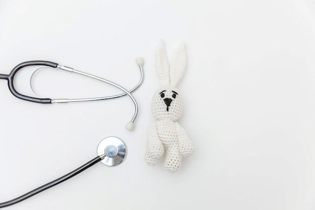 Просто минимальный кролик игрушки дизайна и стетоскоп оборудования медицины изолированные на белой предпосылке. концепция здравоохранения детей доктор. символ педиатра плоская планировка, вид сверху копией пространства