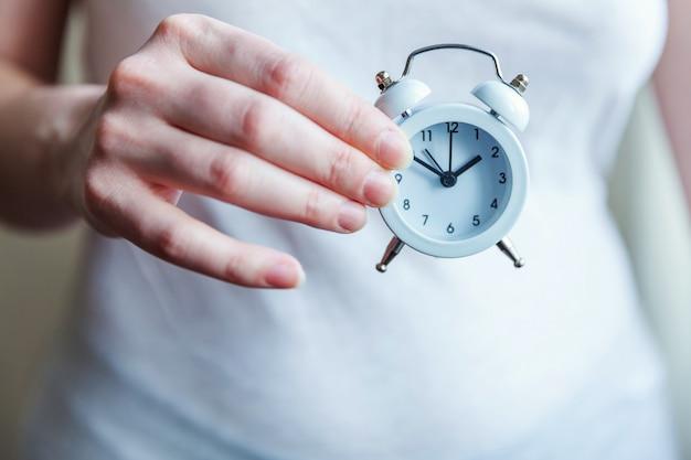 Женские руки женщины держат звенящий двойной звонок старинный классический будильник