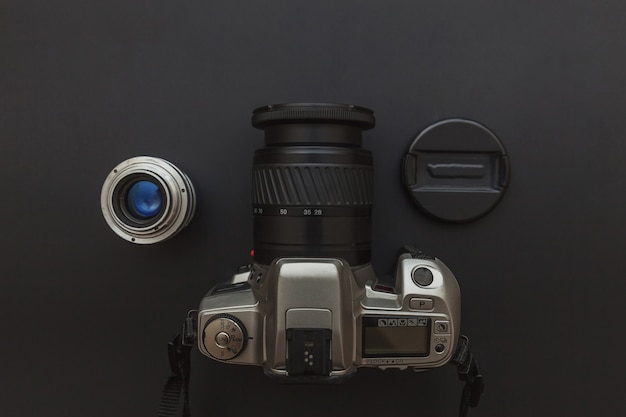 デジタル一眼レフカメラシステムと暗い黒いテーブルの上のレンズの写真家の職場