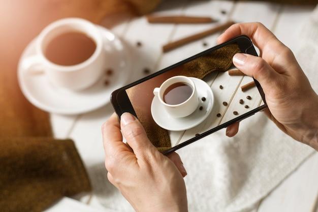 美しい朝食の写真をコーヒースマートフォンに手渡す。ブロガーは社会的な