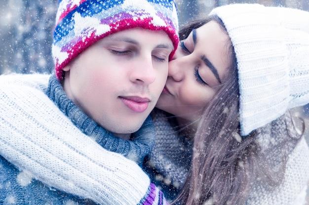 冬の雪の下で幸せな若いカップル。