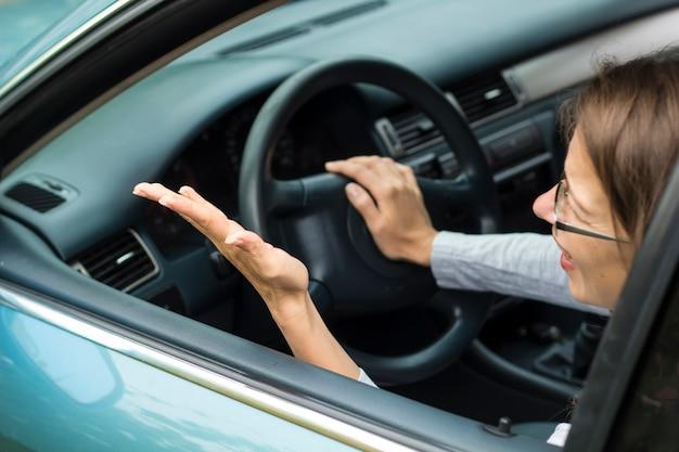 Женщина-водитель нервно сидит в машине. женщина возмущена, кричит.
