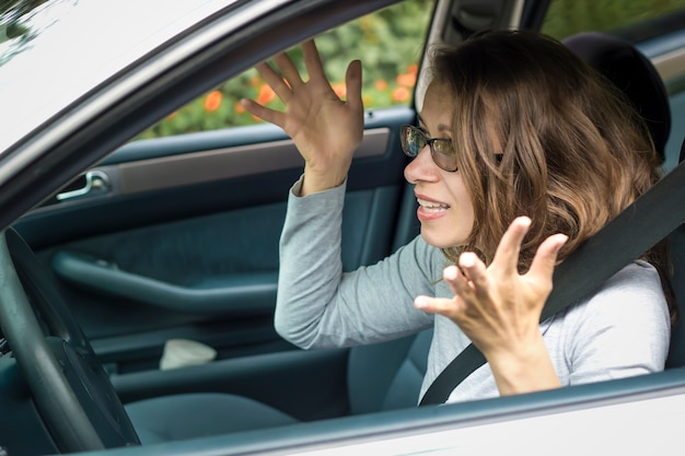 Женщина возмущается, сидя в машине.