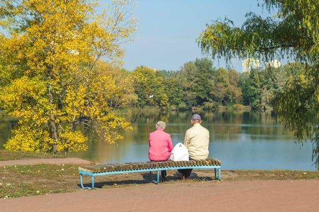 高齢者は一緒にベンチに座って休息しています。恋人のカップルで秋の朝