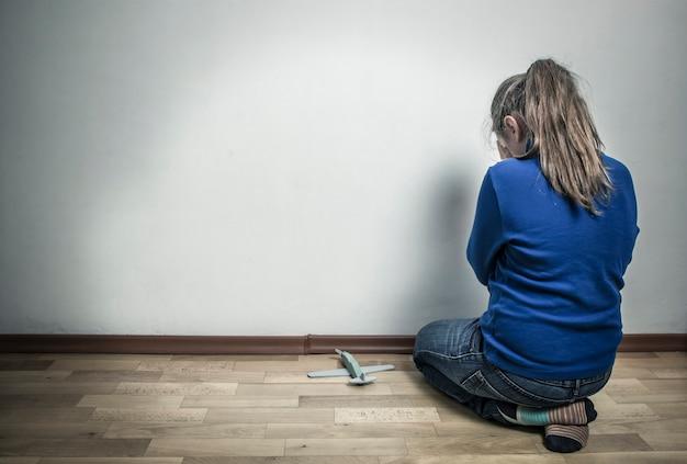 空の部屋に座っている間に泣いている少女。子供は怒っている。自閉症