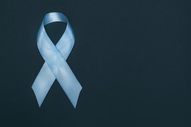黒い背景に青いリボン。前立腺癌の意識の象徴。スペースをコピーします。