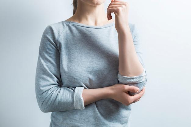 ひじの痛み。女性がひじを痛く抱きしめる損傷。