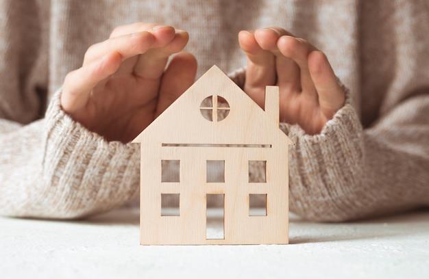 手、不動産保険の概念が付いている家。住宅ローンと税金の支払い。