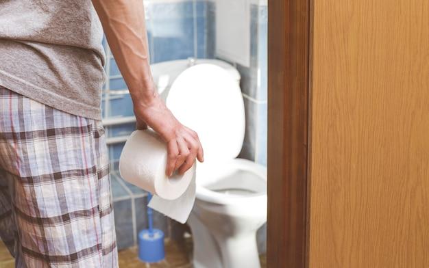 男がトイレットペーパーを持っています。下痢の概念痔。