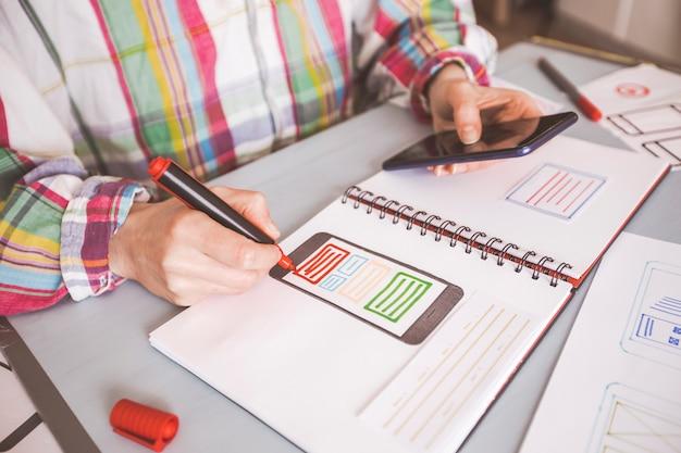 Дизайнер создает веб-приложения для мобильных телефонов.
