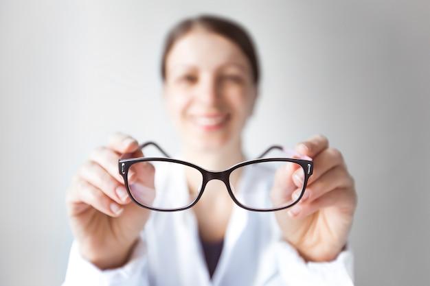 女医眼科医がメガネを保持しています。視覚問題の概念目の光学系