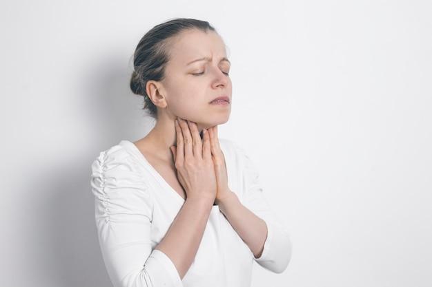 その女性は甲状腺疾患です。喉の痛み。炎症腺。