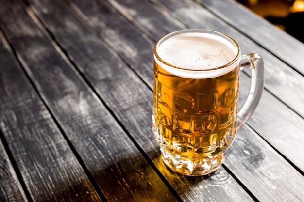 バーの木製テーブルの上の新鮮な軽めのビールのジョッキ。上面図。