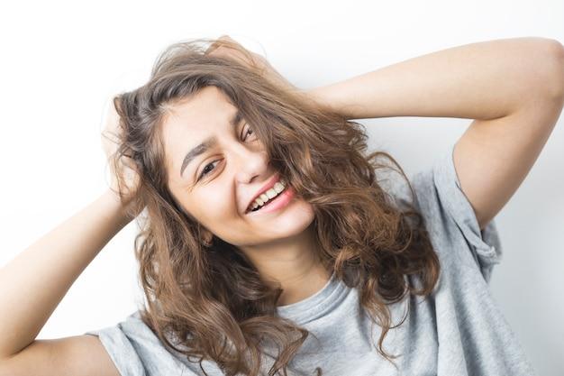 Ся индийская девушка на белой предпосылке. молодая счастливая женщина брюнетка.