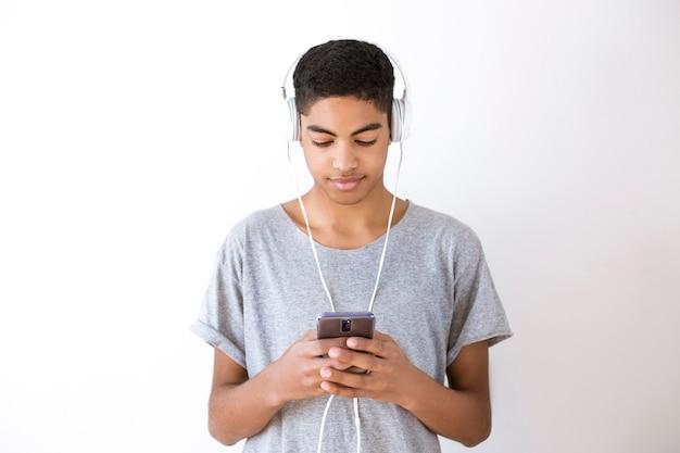 スマートフォンで音楽を聞くヘッドフォンの若い男。