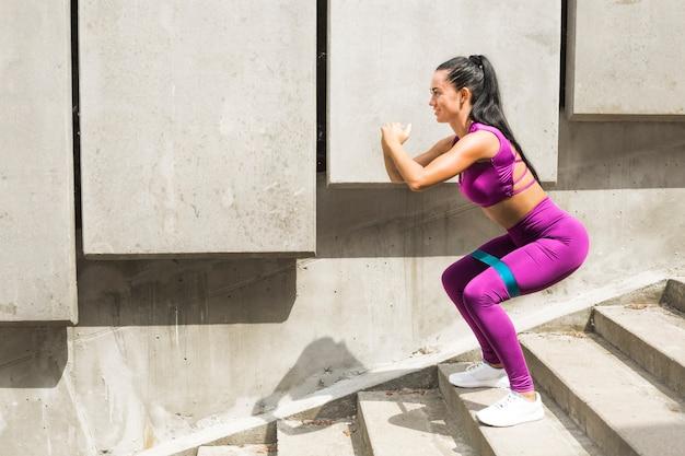 Приседания. сопротивление группа спортивный молодая женщина делает приседания с добычей ремешок растяжения ремня. фитнес женский тренирует резину