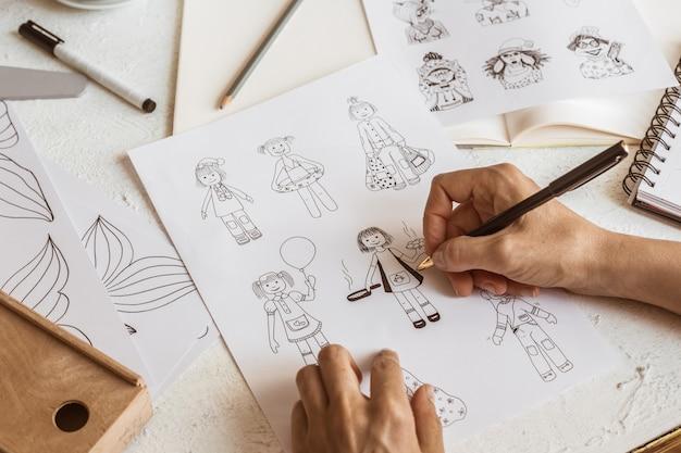 アニメーターデザイナーは、さまざまなキャラクターのスケッチを描きます。
