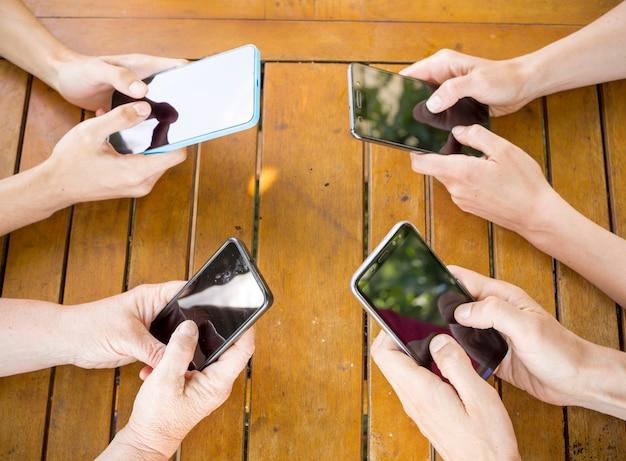 スマートフォンと一緒に楽しんでいる友人のグループ。手でクローズアップの携帯電話。