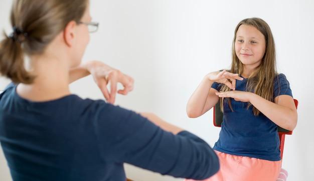 女性は女の子が手話を話すのを教えます。女性は聴覚障害者、ろう者の言葉を話します。