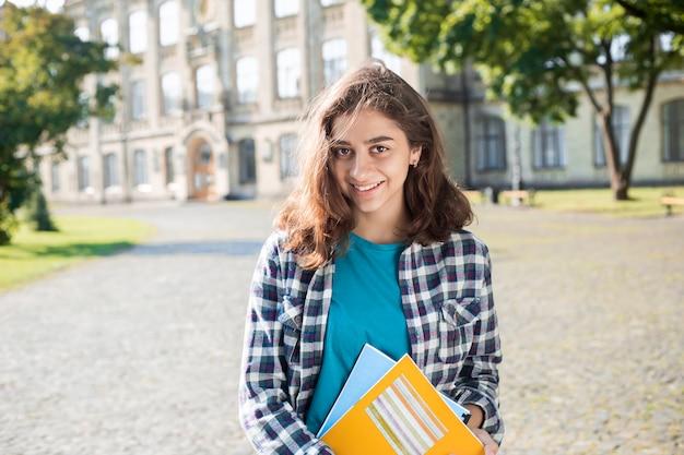 笑顔のインドの若い女子学生は、教育の本を保持しています。大学の近くの幸せなブルネットの少女。