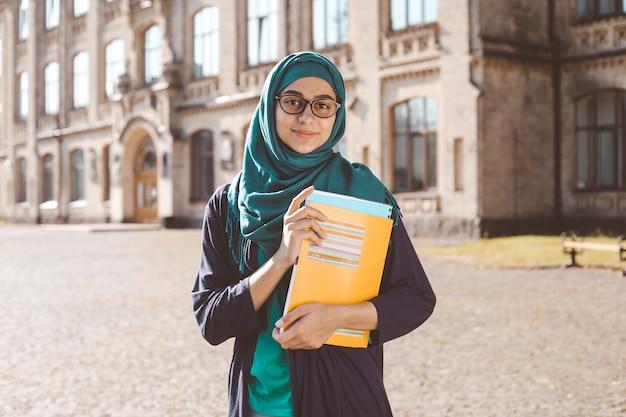 大学の近くに立って本を持って笑顔のイスラム教徒の若い女子学生。ヒジャーブで幸せなアラビアの女の子。トレーニングのアジア女性。