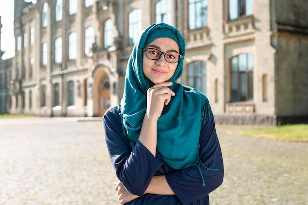 ヒジャーブを着ているイスラム教徒のイスラムの若いビジネス女性の笑みを浮かべてください。メガネで幸せなアラブの女子生徒。