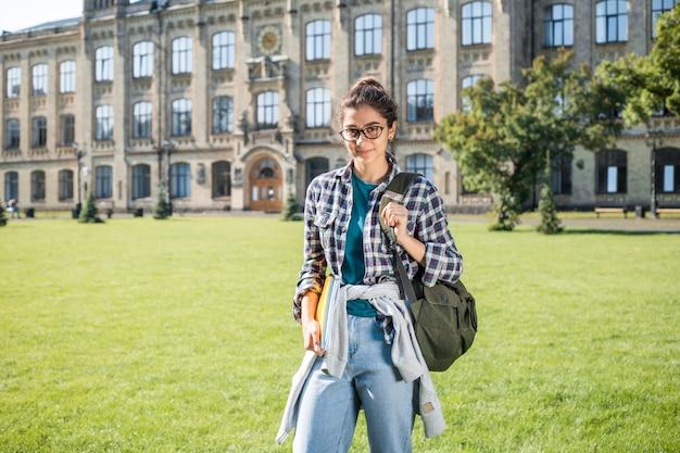 美しいインドの女子学生は大学の近くに立っています。本を持ってメガネで幸せな若いブルネットの女性。