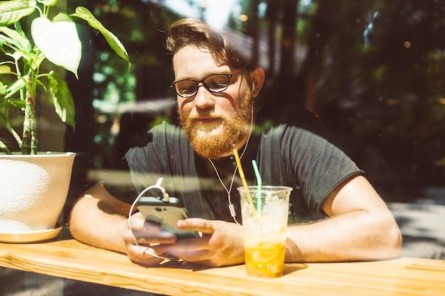 カフェに座っているスタイリッシュなひげを生やした赤毛の若い男